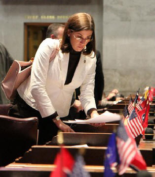 In a Monday, Feb. 7, 2011 photo, state Rep. Julia Hurley gathers her papers on the House floor in Nashville, Tenn. The Lenoir City Republican, in the latest edition of Hooters Magazine, attributes her business and political success to her time working at the restaurant chain known for its waitresses' revealing outfits.