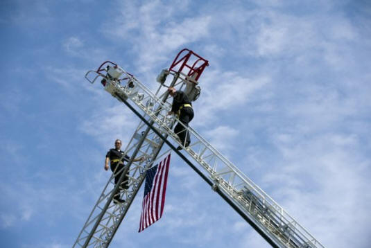 For Loudon Bridge Day, the city of Loudon Fire Department, left, and the Lenoir City Fire Department used their ladder trucks to hang a flag over the Veterans Memorial-John Duncan Bridge on Sunday, September 11, 2011.      (Saul Young/News Sentinel)
