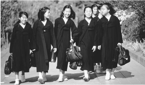 A group of North Korean girls walk to school. Education in North Korea is geared toward furthering the influence of state socialism.